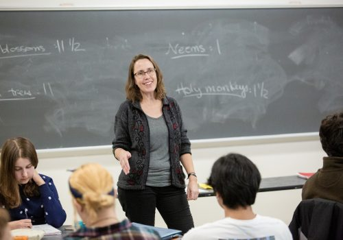 A professor lecturing students with a chalkboard in the background.