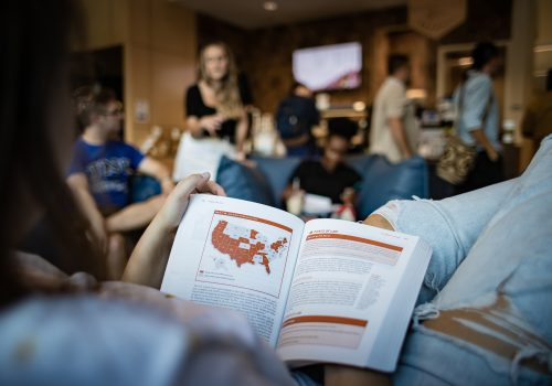 A student reading a textbook with a map of the U.S. with some states highlighted in red.