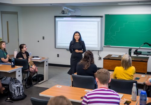 A professor lecturing students using a powerpoint presentation.